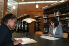 Two students studying in a library.